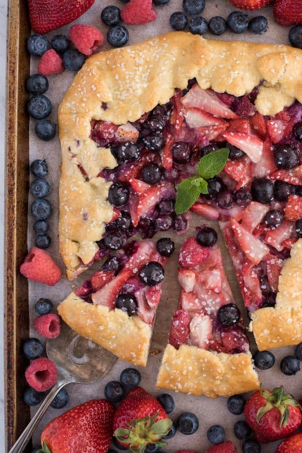 aerial photo of mixed berry galette on baking sheet with strawberries, blueberries, and raspberries