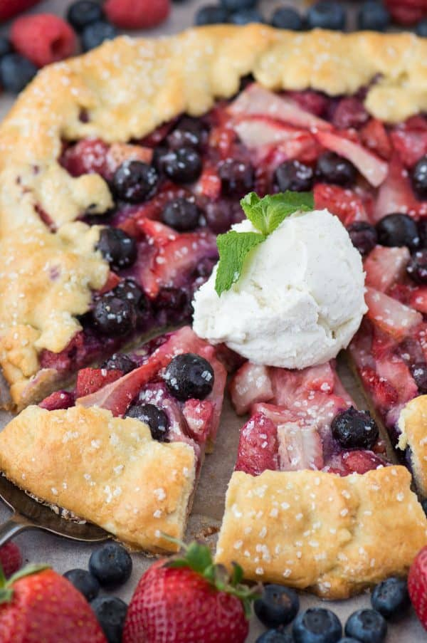 mixed berry galette with strawberries and blueberries on metal baking sheet with scoop of vanilla ice cream on top