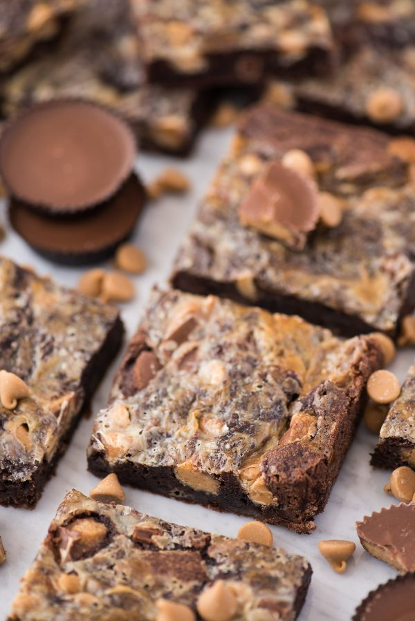 reese's magic bars on white background with peanut butter chips scattered