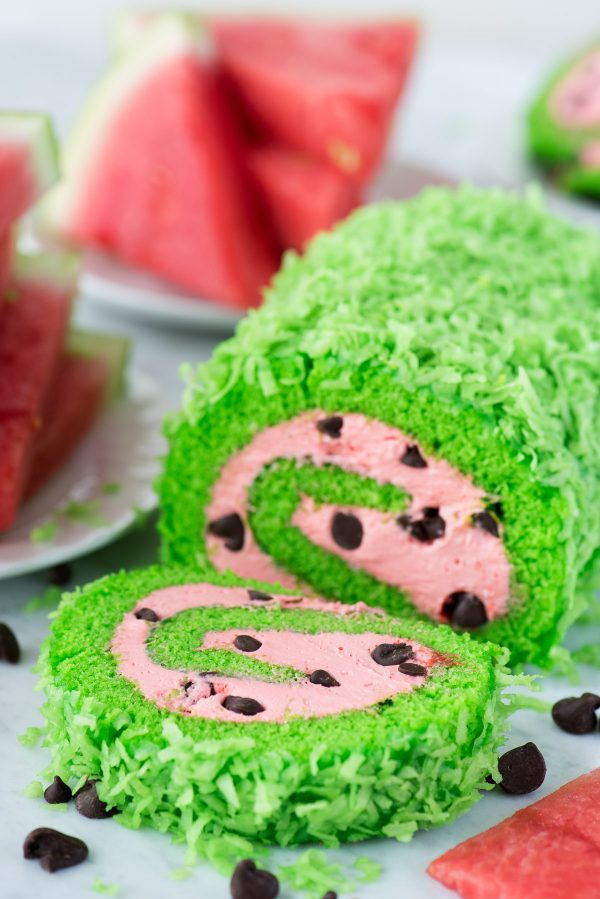 green cake roll with pink filling and chocolate chips to look like a watermelon cake roll
