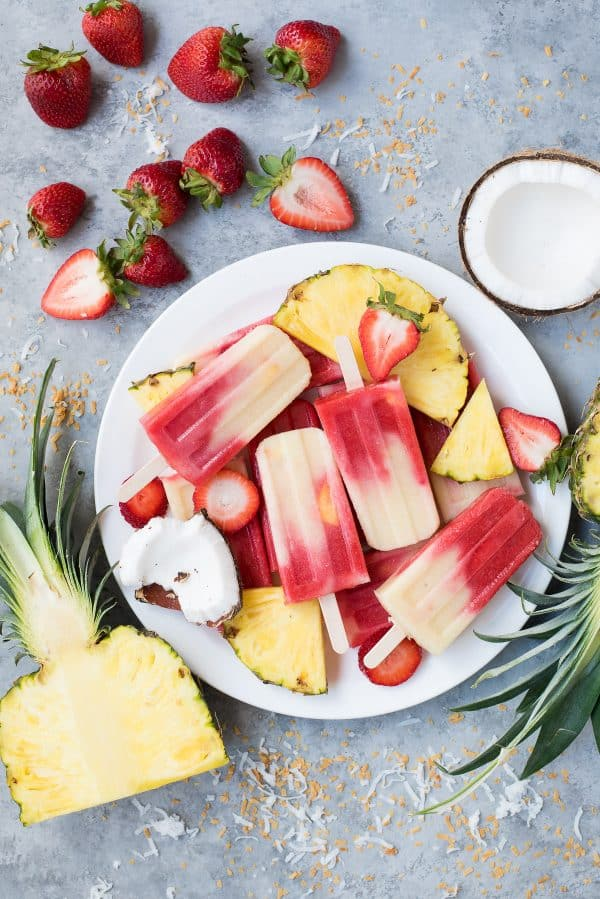 strawberry and coconut layered popsicles on white plate on gray background