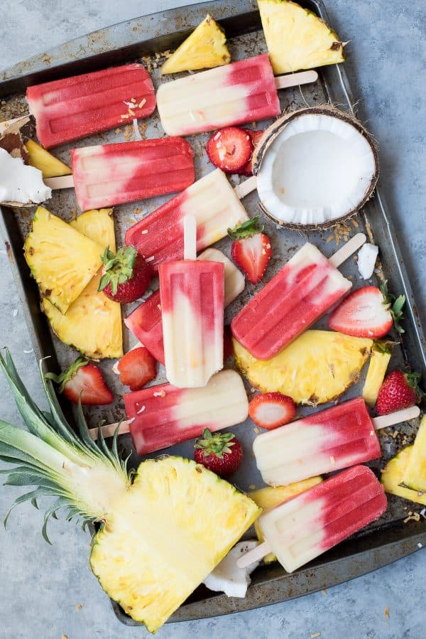 strawberry and coconut layered popsicles on metal tray on gray background