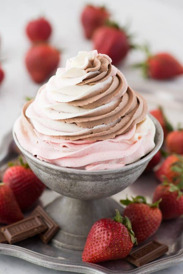 neapolitan whipped cream piped into a metal bowl with strawberries in the background