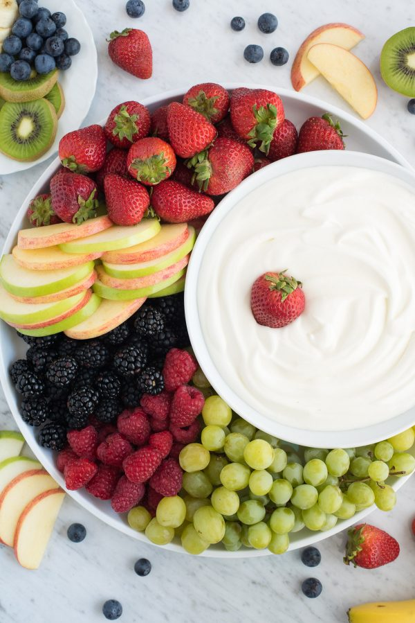 round platter filled with strawberries, apples, blackberries, raspberries and grapes with a bowl of white fruit dip