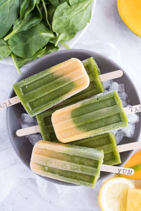Green spinach and mango layered popsicles in a gray bowl on a white background