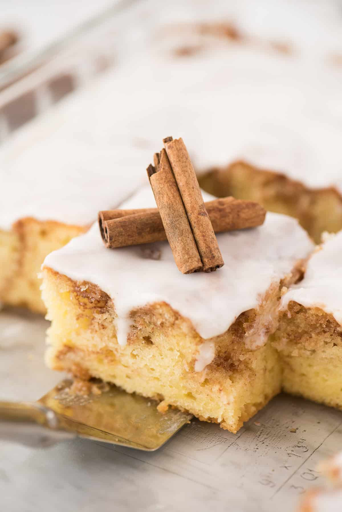 a piece of cinnamon swirl cake in glass pan with white glaze on top and 2 cinnamon sticks