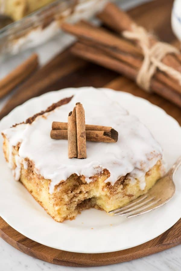 a piece of cinnamon swirl cake on white plate with white glaze on top and 2 cinnamon sticks
