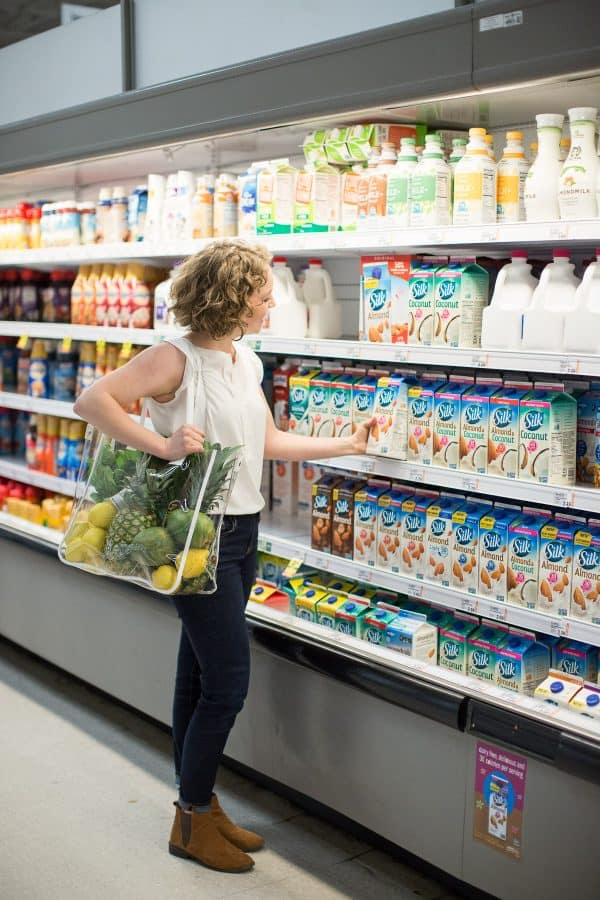 Woman standing in grocery store reaching for almondmilk