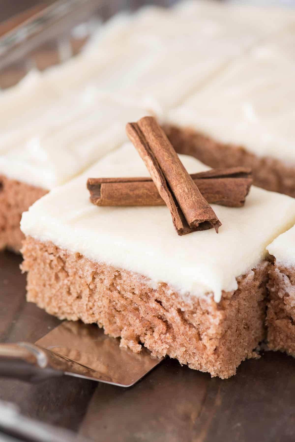 a piece of cinnamon spice cake with cream cheese frosting with 2 cinnamon sticks on top