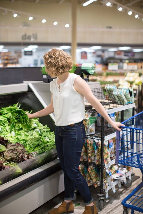woman shopping for spinach in a grocery store