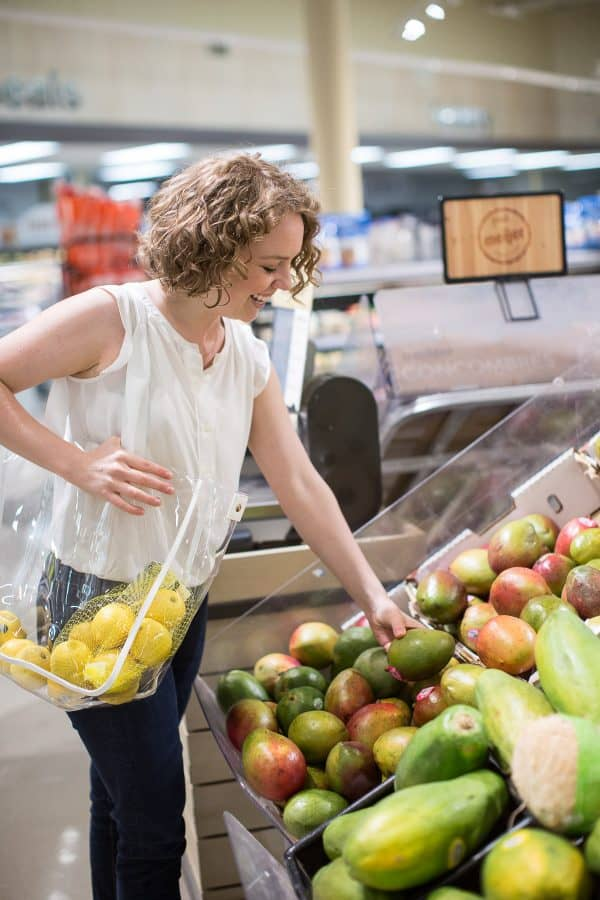 woman shopping for mango in a grocery store