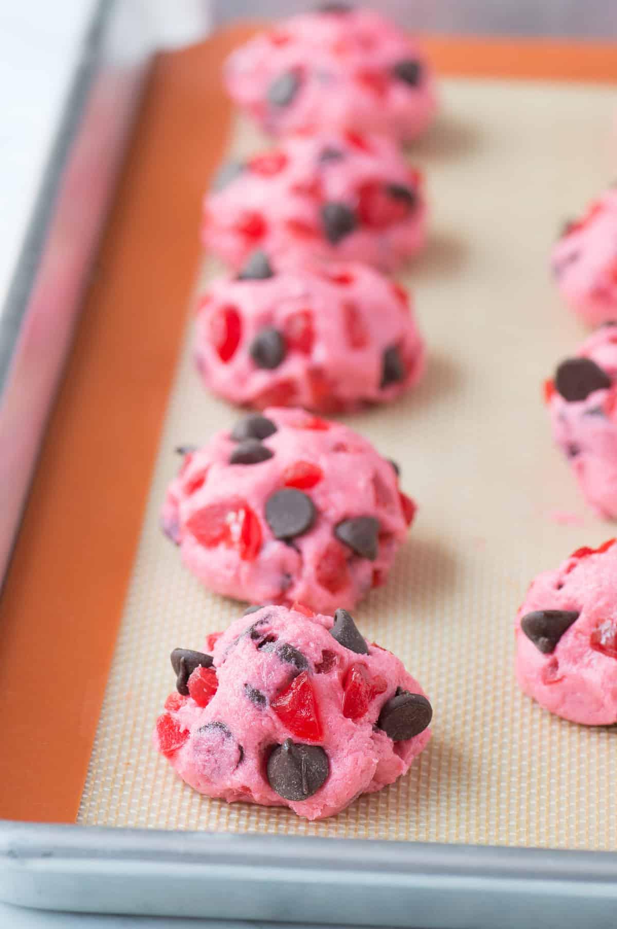 pink maraschino cherry chocolate chip cookies on baking sheet before baking