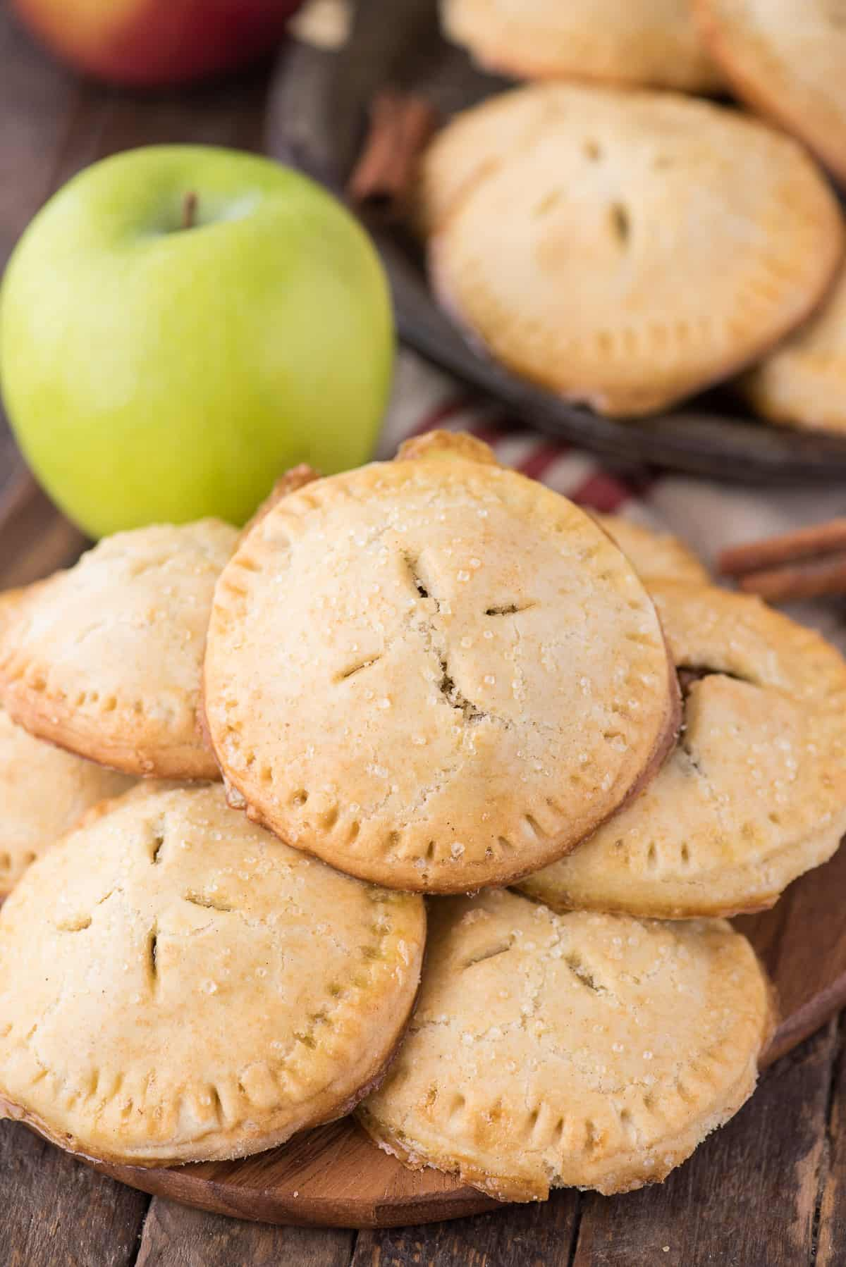 a stack of apple hand pies on wood background with green apple in the background