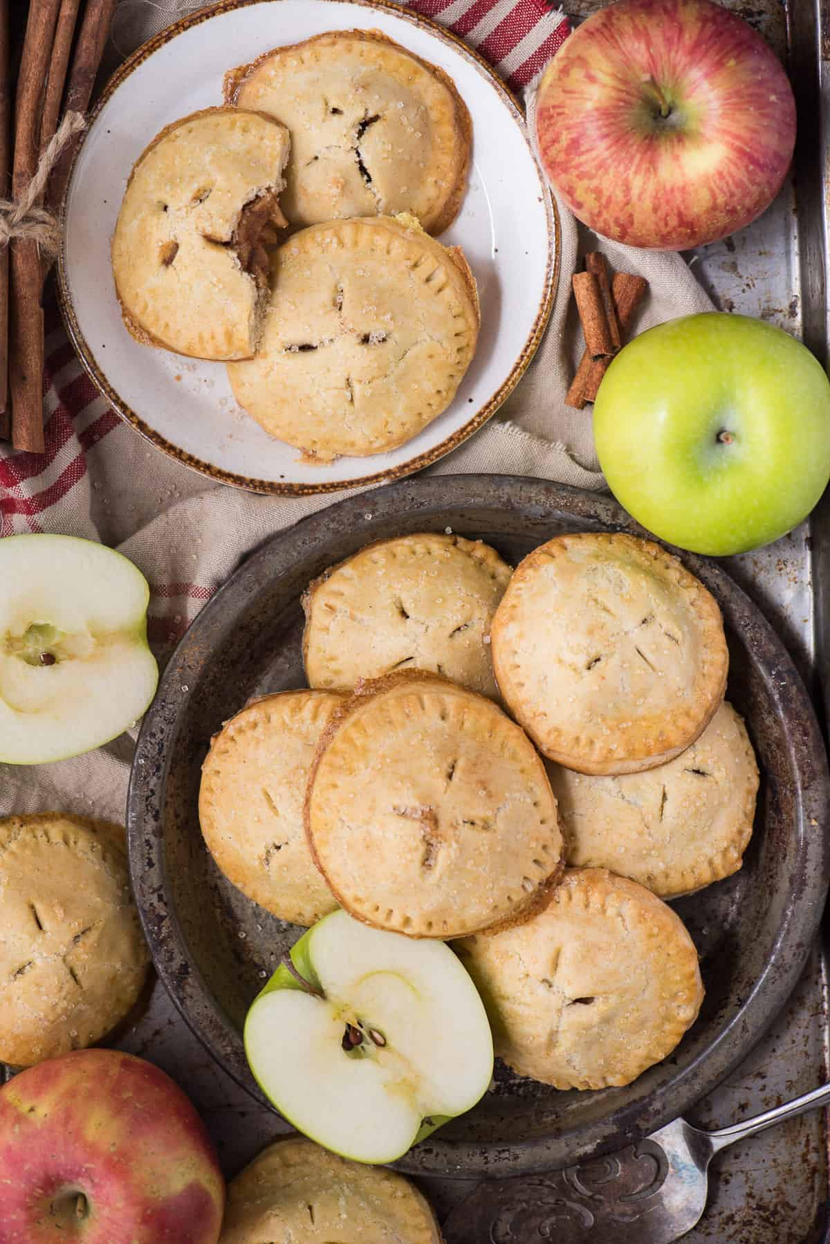 apple hand pies on plates with apples and tan colored napkin