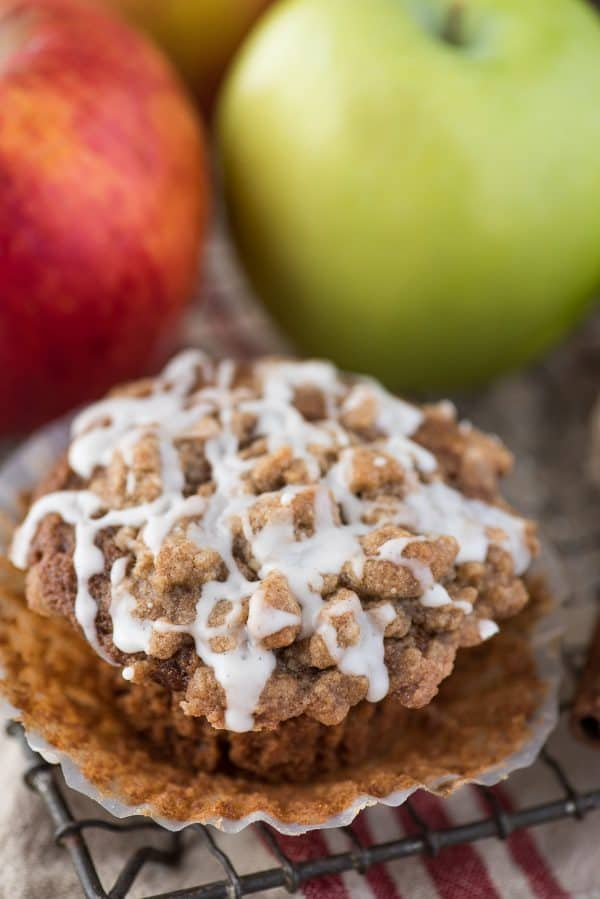 applesauce spice muffins with crumb topping and white glaze on wire rack and apples in the background