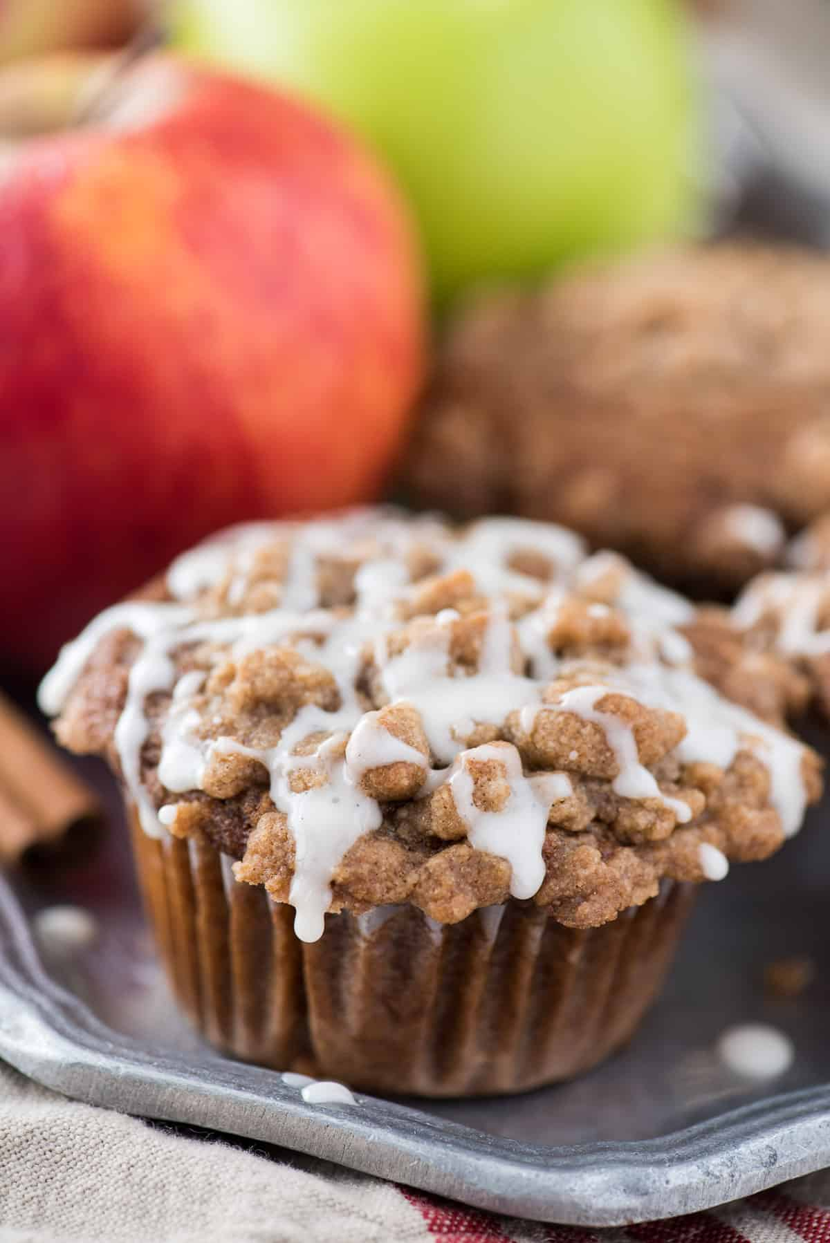 applesauce spice muffins with crumb topping and white glaze on metal plate and apples in the background