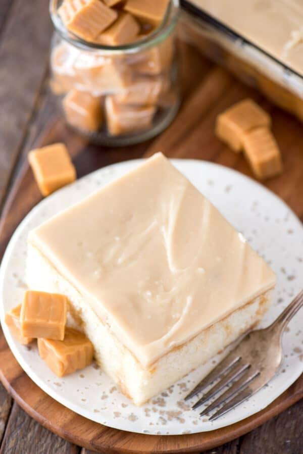 slice of caramel cake on white plate on wood background