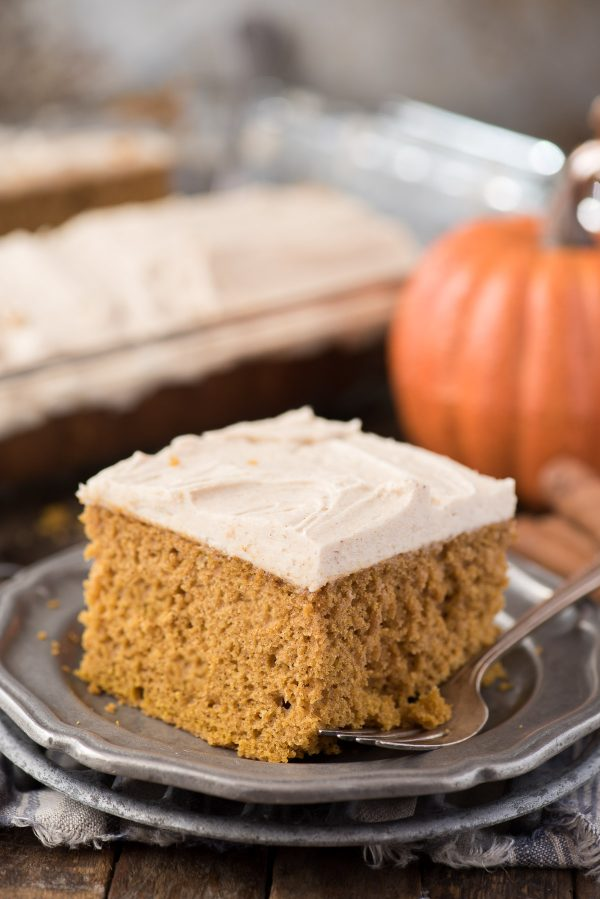 slice of doctored up pumpkin cake on metal plate with pumpkin in background