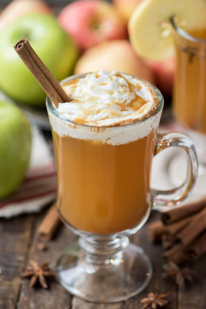 hot apple cider in clear glass with whipped cream and a cinnamon stick