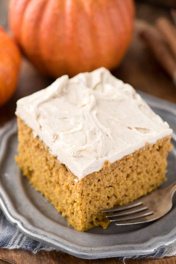 slice of pumpkin cake on metal plate with pumpkin in background