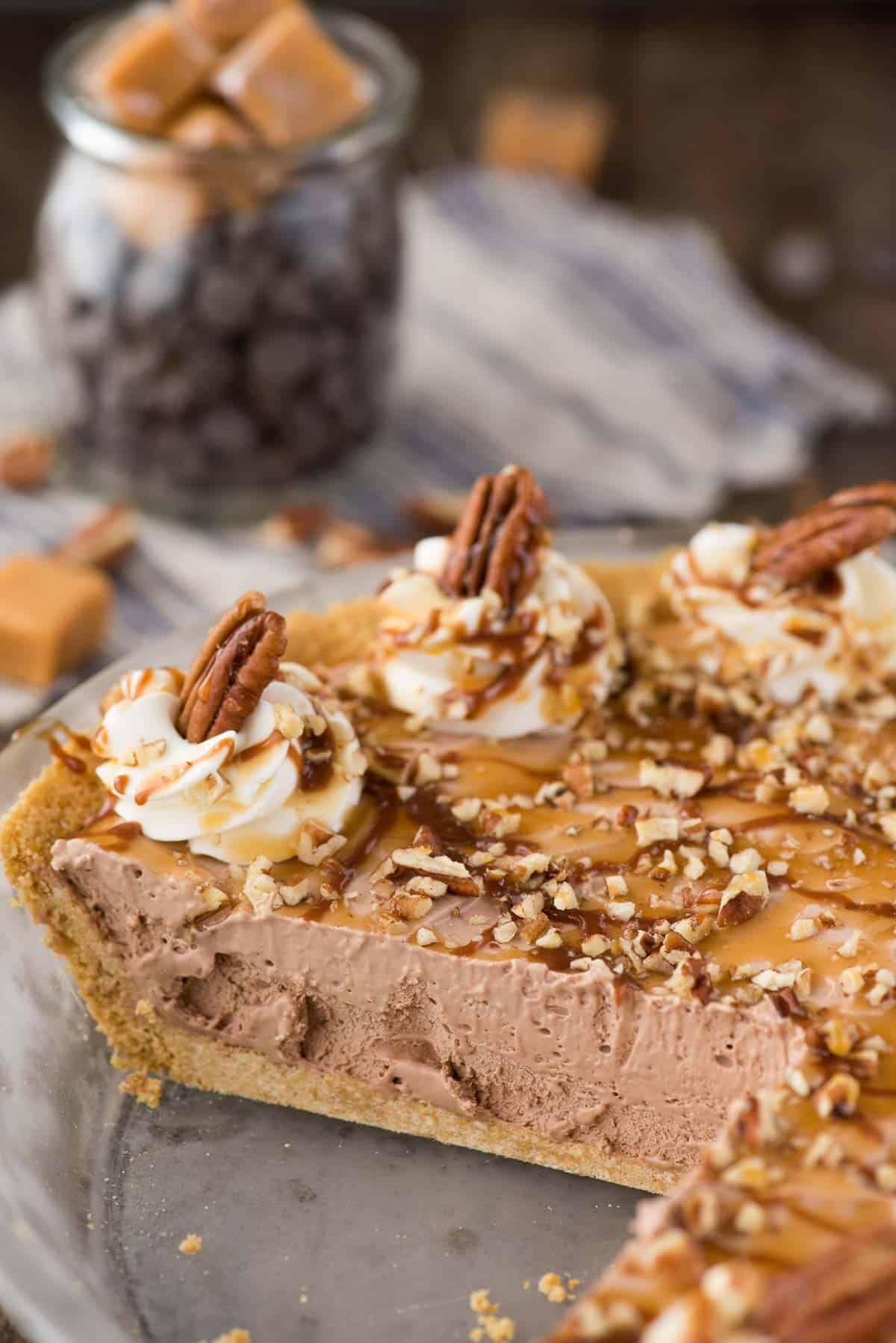 turtle pie with chocolate filling, chopped pecans and caramel drizzle in glass pie pan