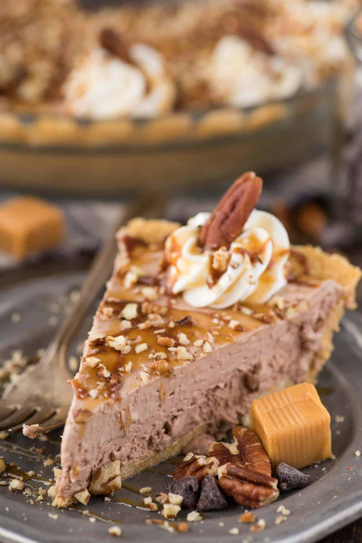 slice of turtle pie with chocolate filling, chopped pecans and caramel drizzle on metal plate