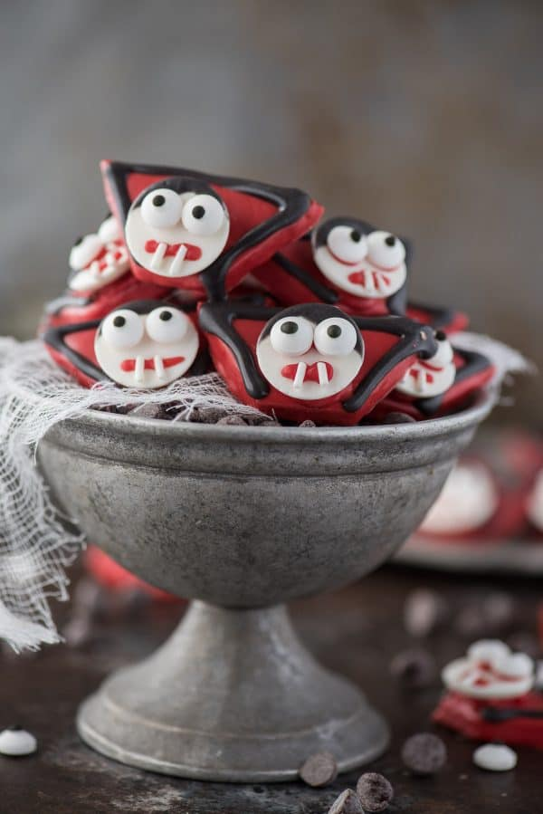 edible vampire treats made out of graham crackers and candy melts displayed in metal bowl