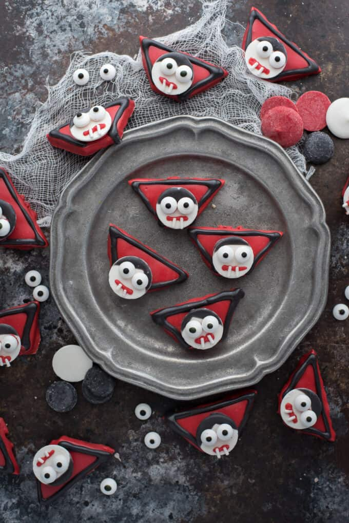 edible vampire treats made out of graham crackers and candy melts displayed on dark background