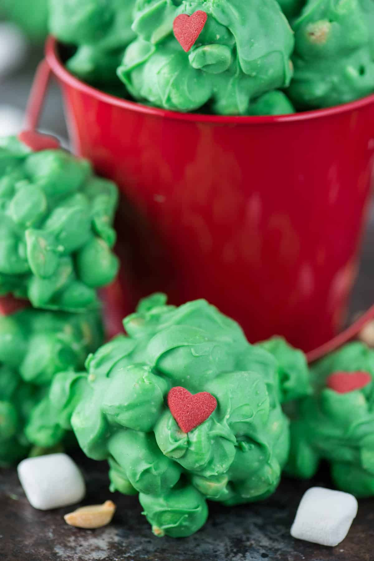 peanut marshmallow clusters coated in green chocolate with a red candy heart for grinch clusters!