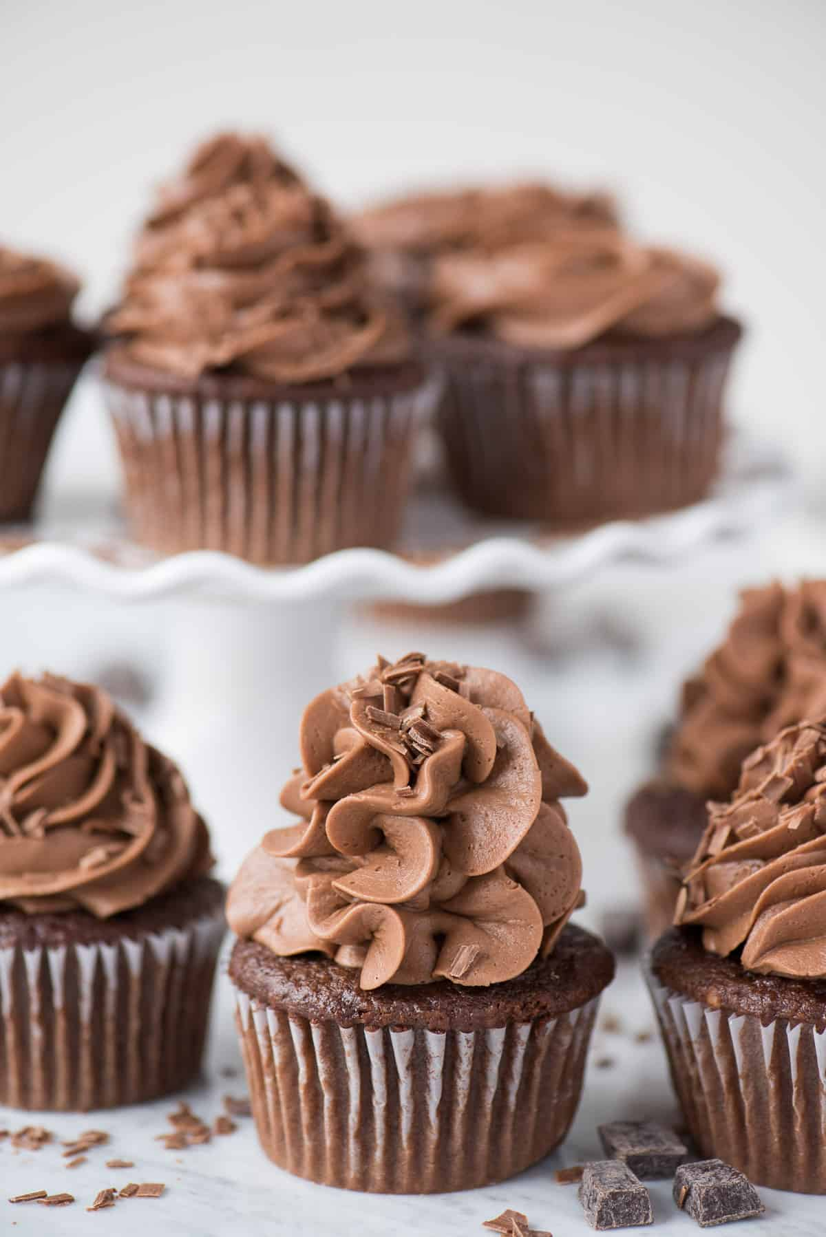 chocolate cupcakes with chocolate frosting on white background