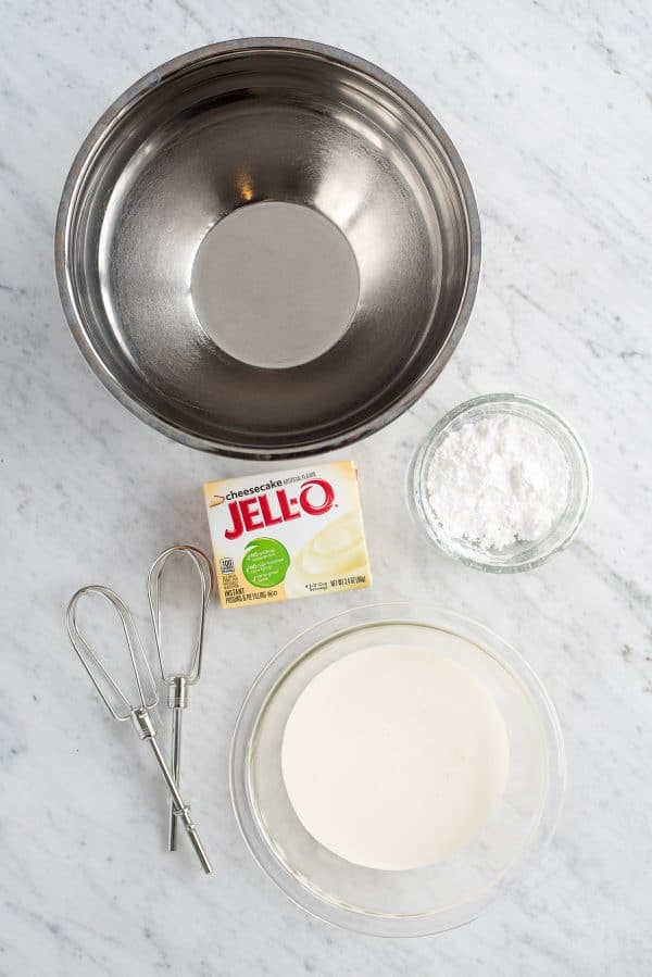 ingredients to make cheesecake whipped cream - metal bowl, powdered sugar, heavy cream, cheesecake flavored instant pudding mix and beaters