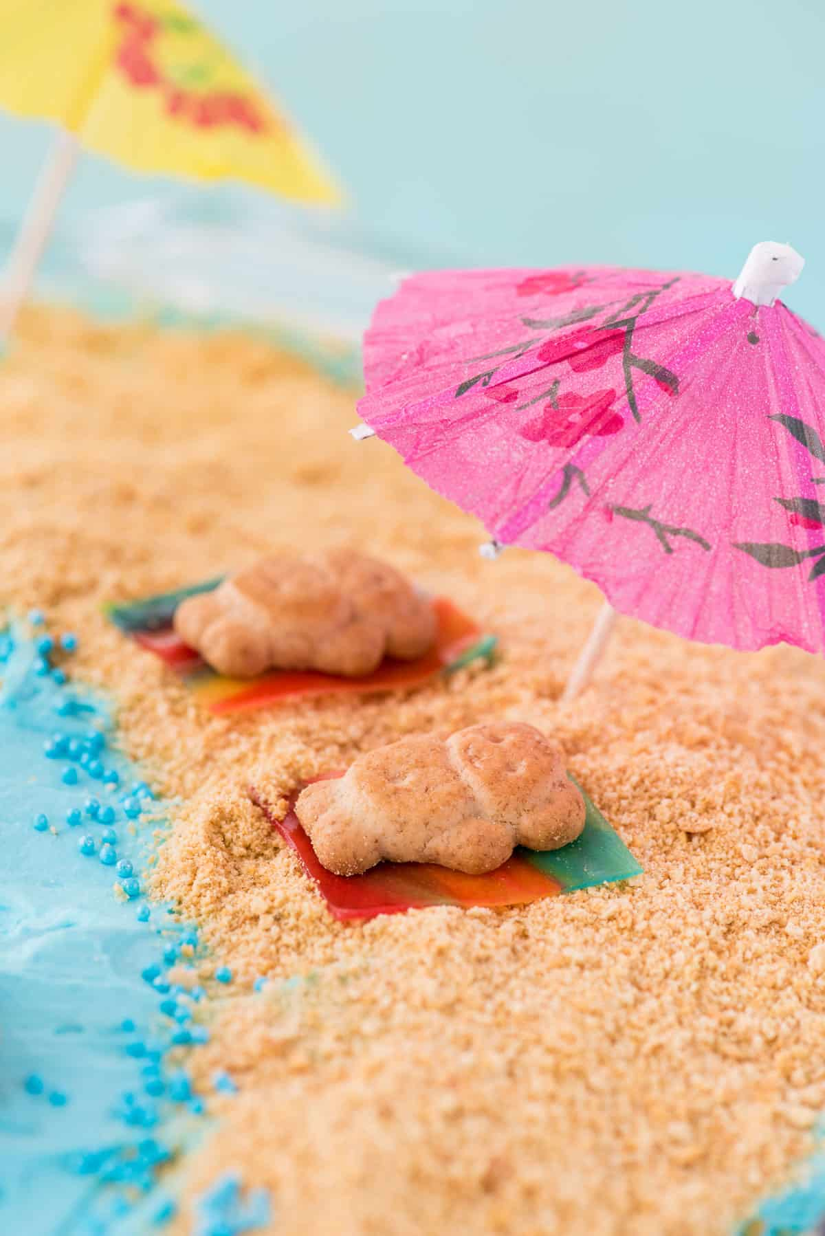 beach theme cake, teddy grahams on fruit roll up towels sitting on graham cracker sand under a toothpick umbrella