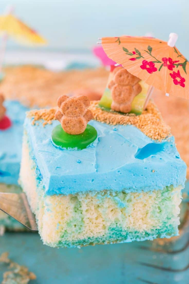This beach theme poke cake would be a hit at a beach theme party or under the sea theme party! Kids will have fun decorating the top of this beach cake with teddy grahams, gummy sea creatures, and graham cracker sand. #beachpokecake #pokecake #beachcake