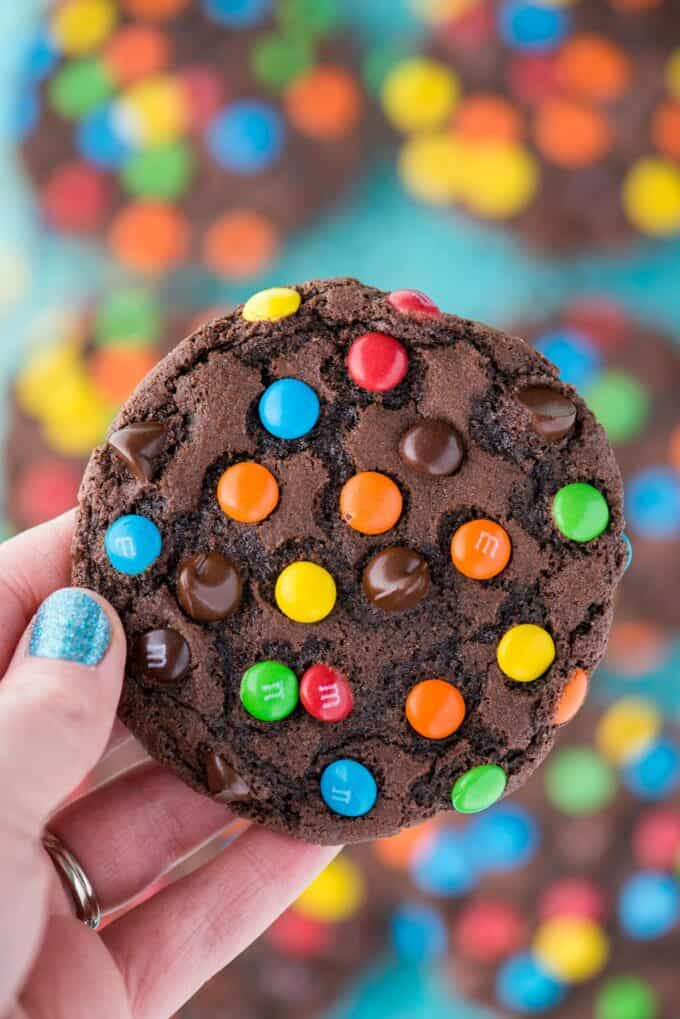 hand holding double chocolate chip cookie with m&ms and chocolate chips