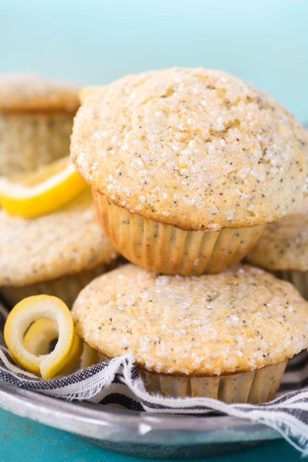 lemon poppy seed muffins stacked on top of each other in metal dish with blue striped cloth