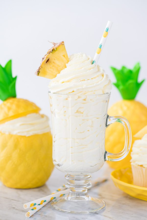 pineapple whipped cream in glass cup with a pineapple piece and pineapple printed straw