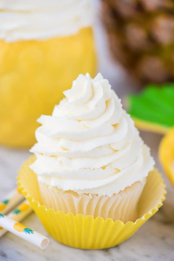 pineapple whipped cream frosting piped onto white cupcake