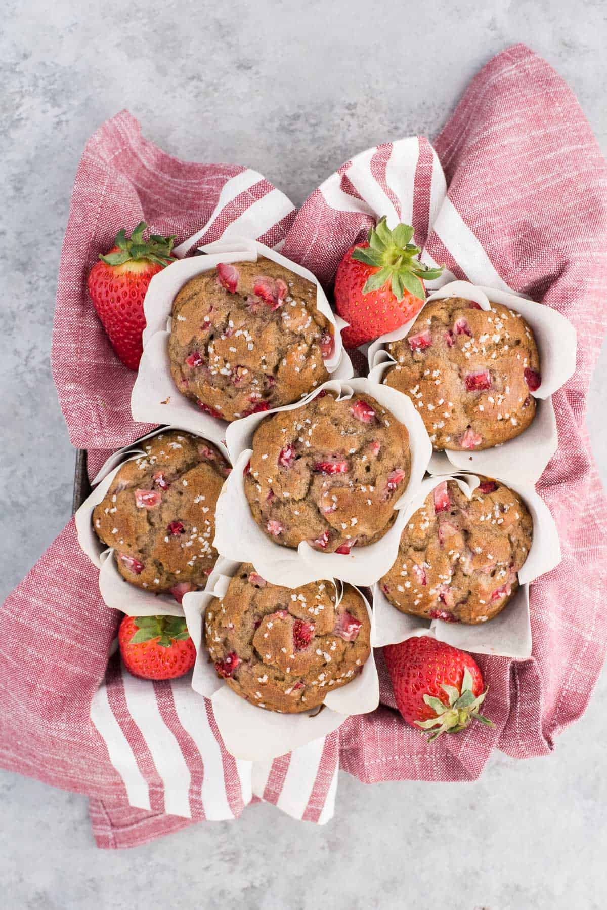 strawberry banana muffins in white parchment paper liners on red and white striped towel