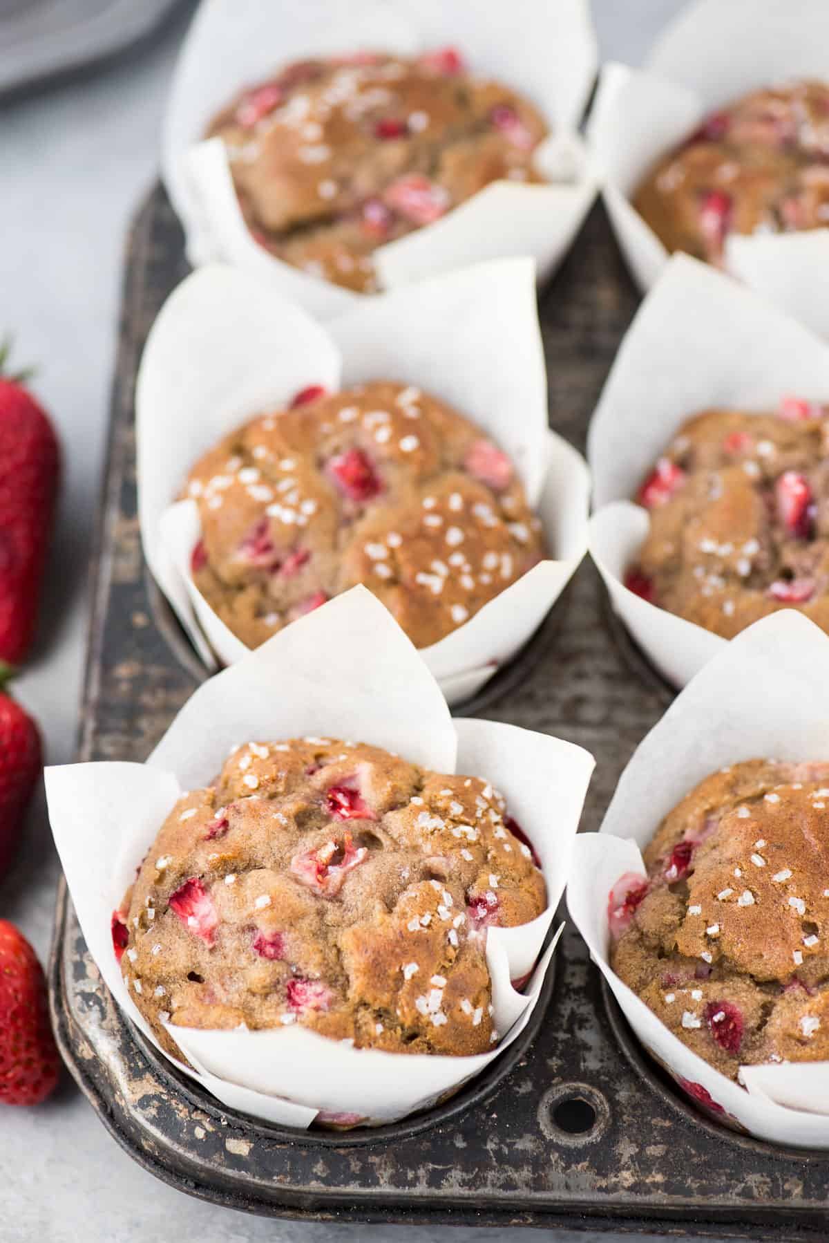strawberry banana muffins in white parchment paper liners in metal muffin tin