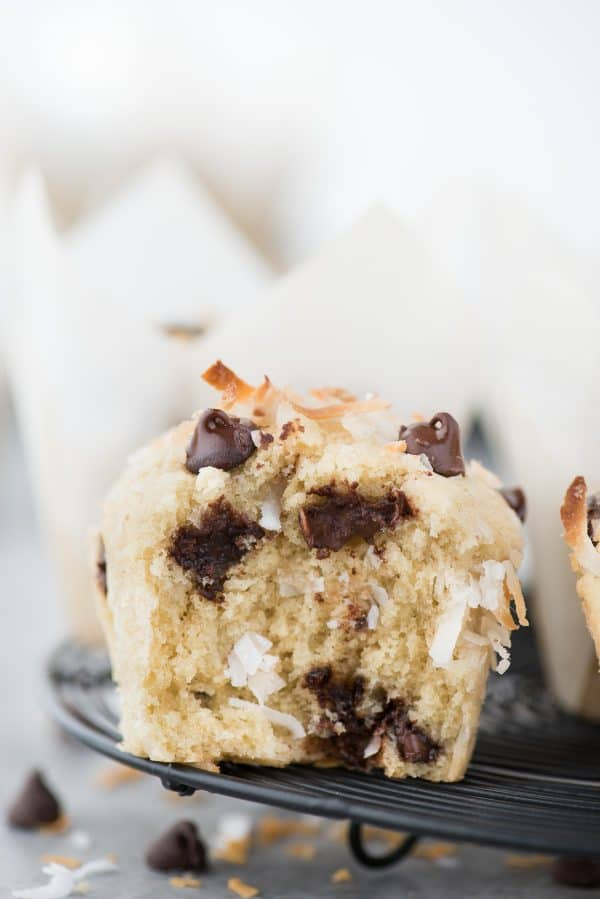 Coconut chocolate chip muffin with bite taken out of muffin on black wire cooling rack