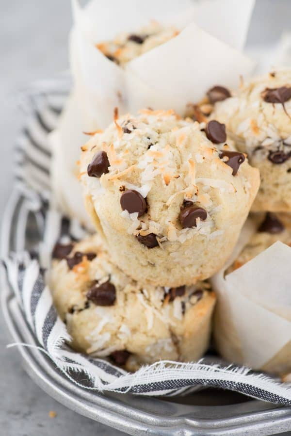 Coconut chocolate chip muffins stacked in a tower on metal platter with blue and white stripe towel