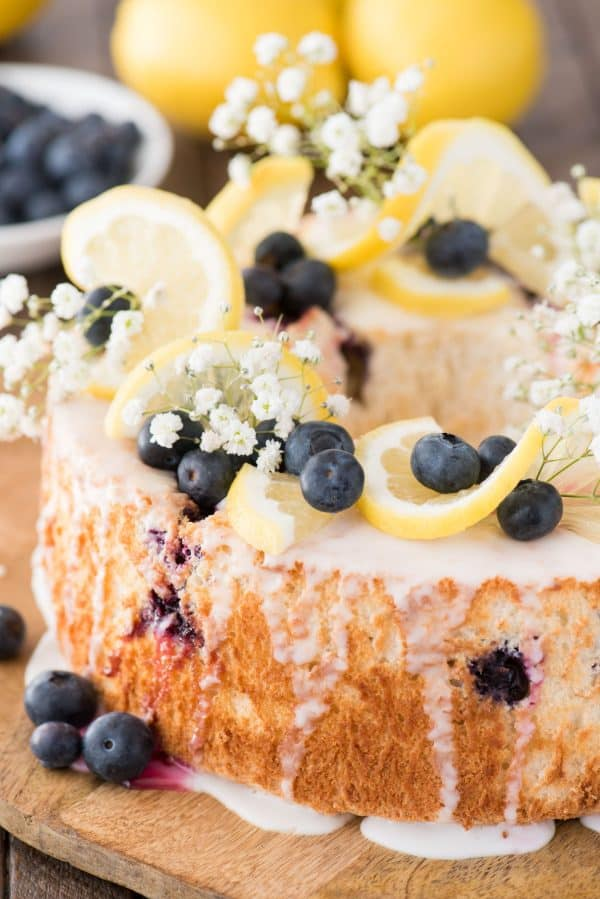Lemon blueberry angel food cake with lemon slices, blueberries and baby's breath as garnish on top of the cake on a wood serving plate.