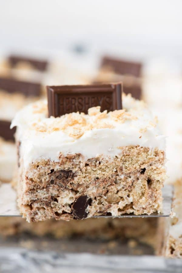 Rice krispie s'mores treat with marshmallow frosting topped with hershey's bar on metal serving utensil