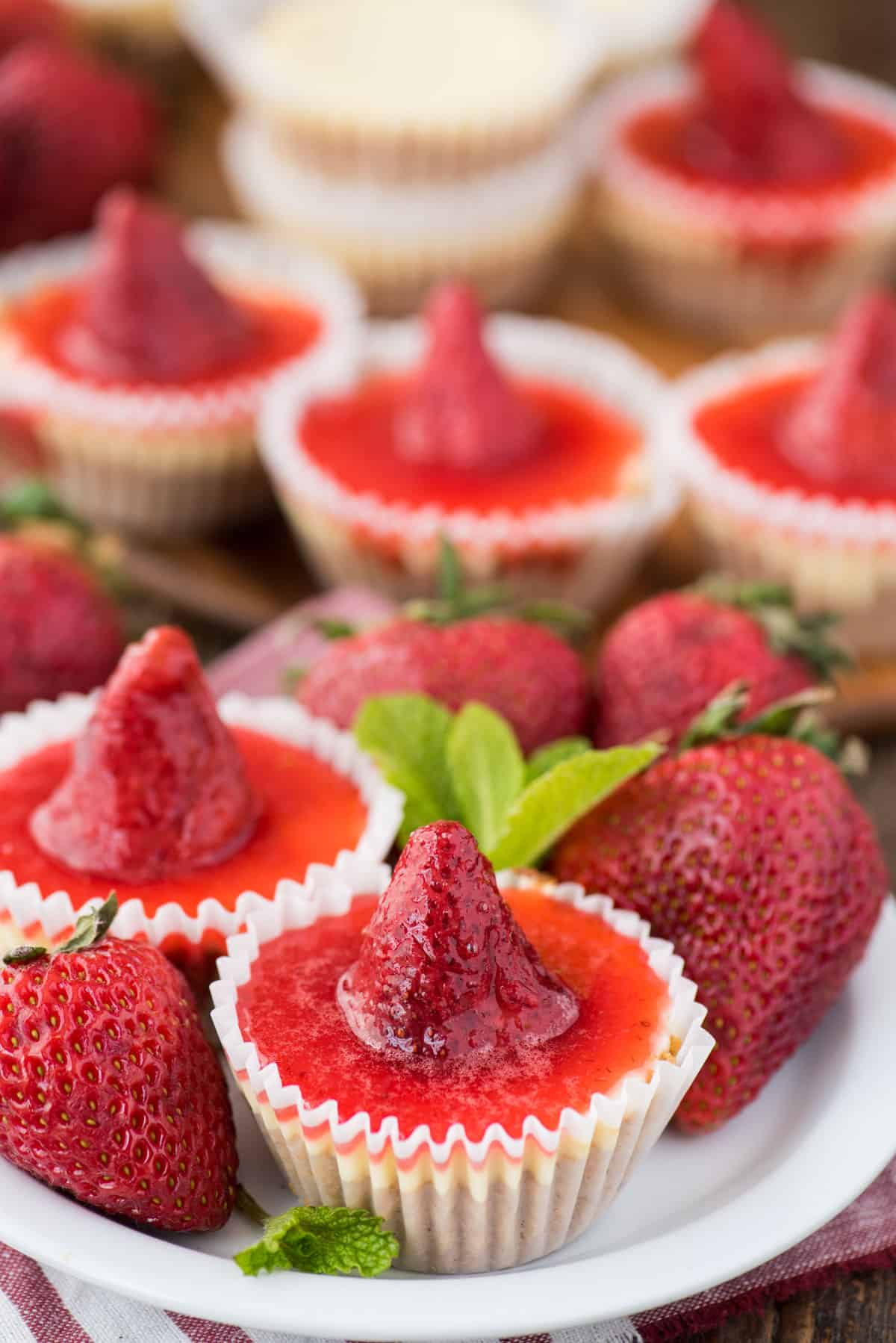 mini plain cheesecakes with strawberry topping on white serving tray
