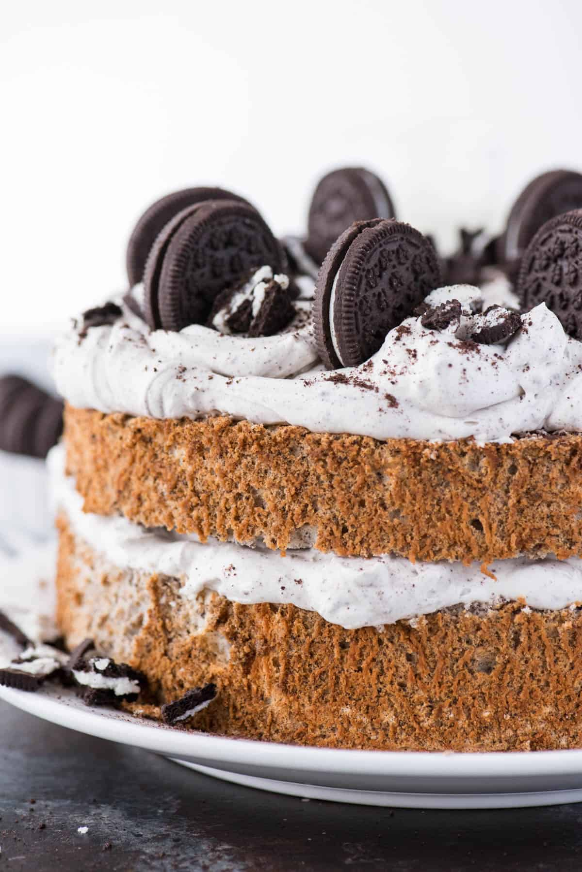oreo angel food cake with oreo whipped cream and crushed oreo pieces on white plate on dark background