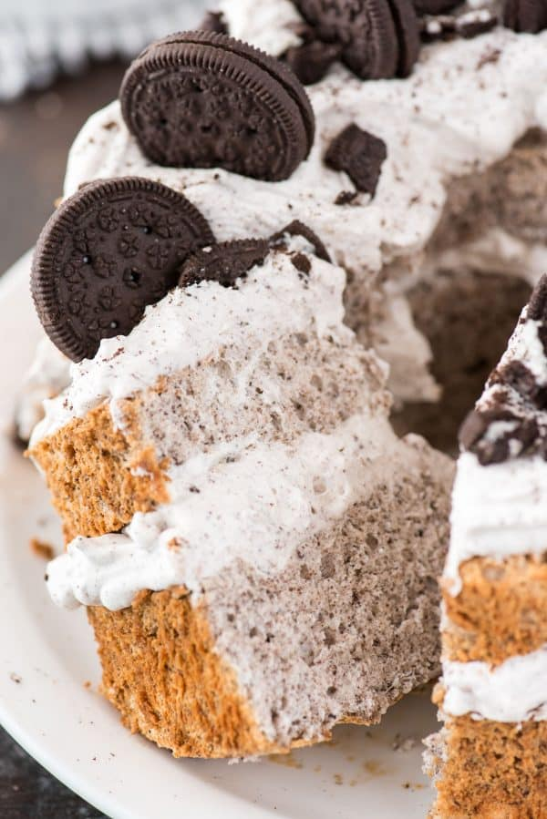 slice of oreo angel food cake with oreo whipped cream and crushed oreo pieces on white plate on dark background
