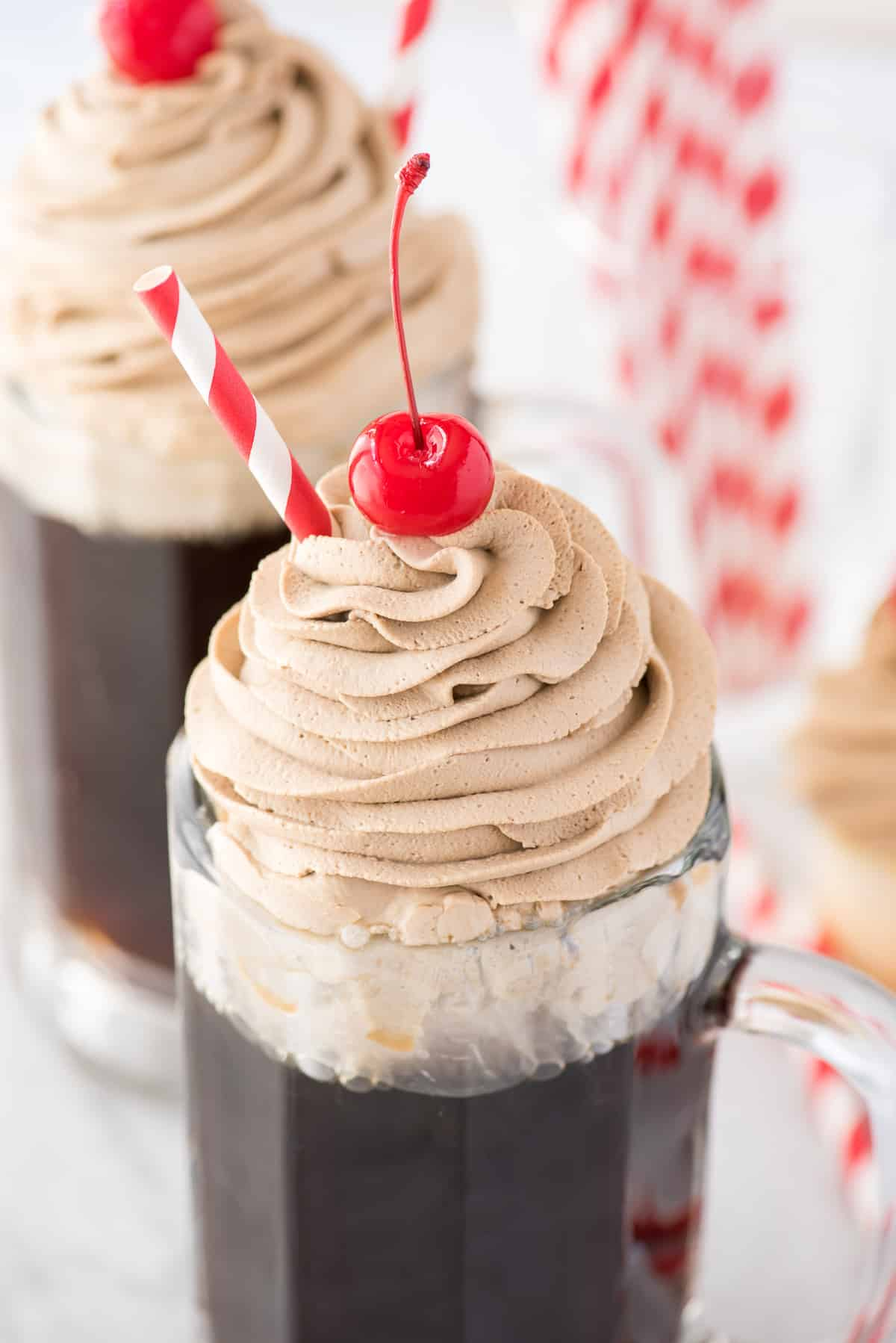 root beer whipped cream piped on top of root beer in a mug with maraschino cherry and red straw