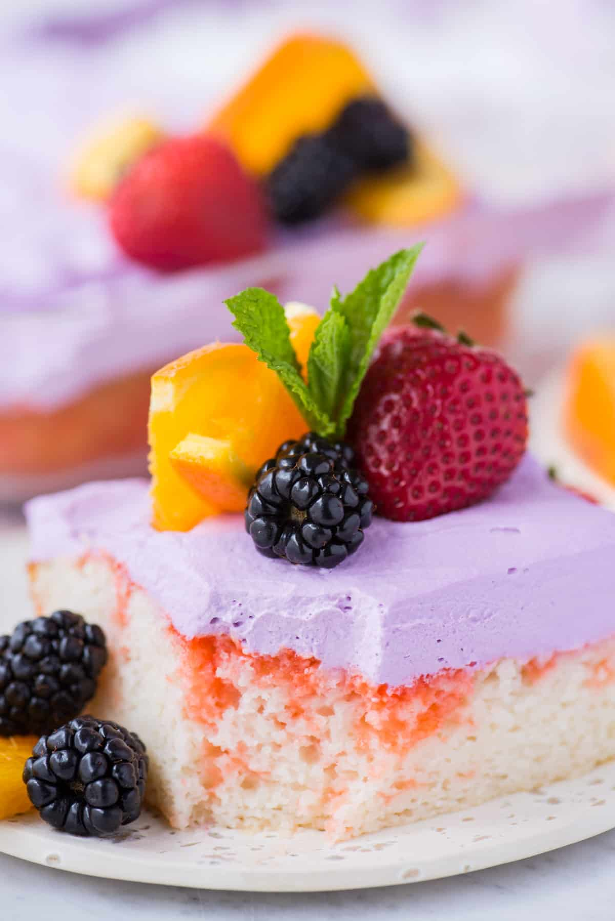 slice of sangria poke cake garnished with a strawberry, blackberries, orange slice and mint leaf on white plate