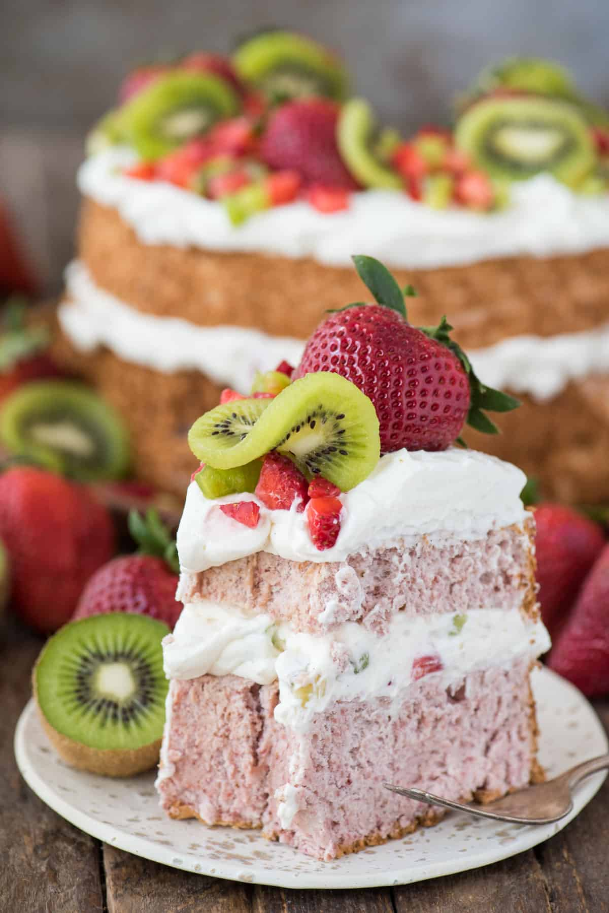 slice of strawberry angel for cake with whipped cream, strawberries and kiwi on white plate