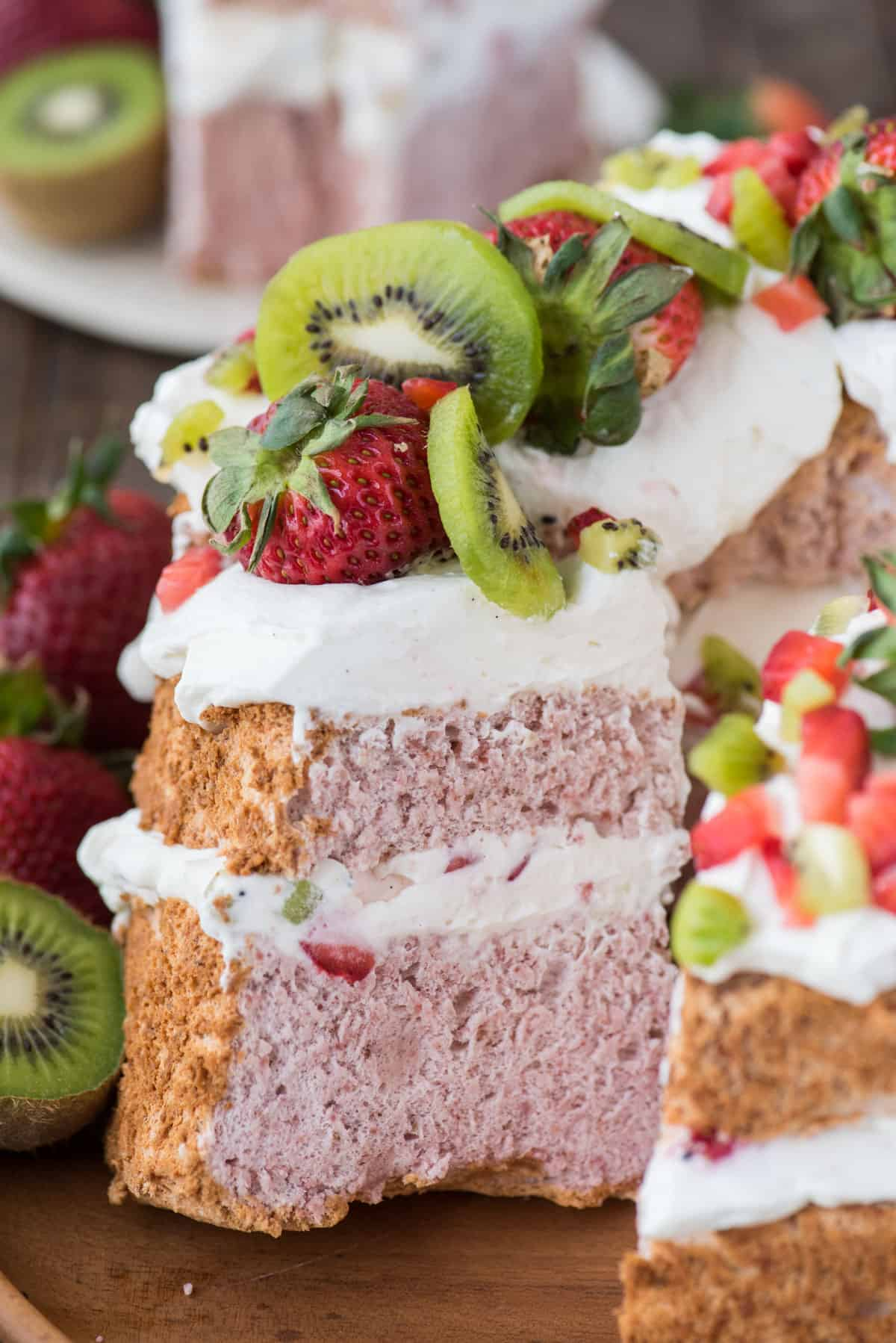 slice of strawberry angel for cake with whipped cream, strawberries and kiwi